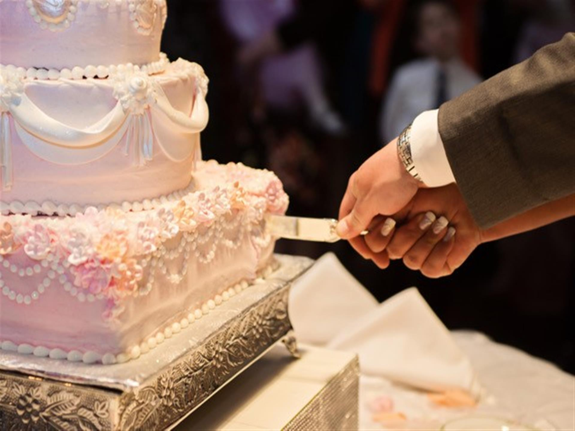 couple cutting into a wedding cake