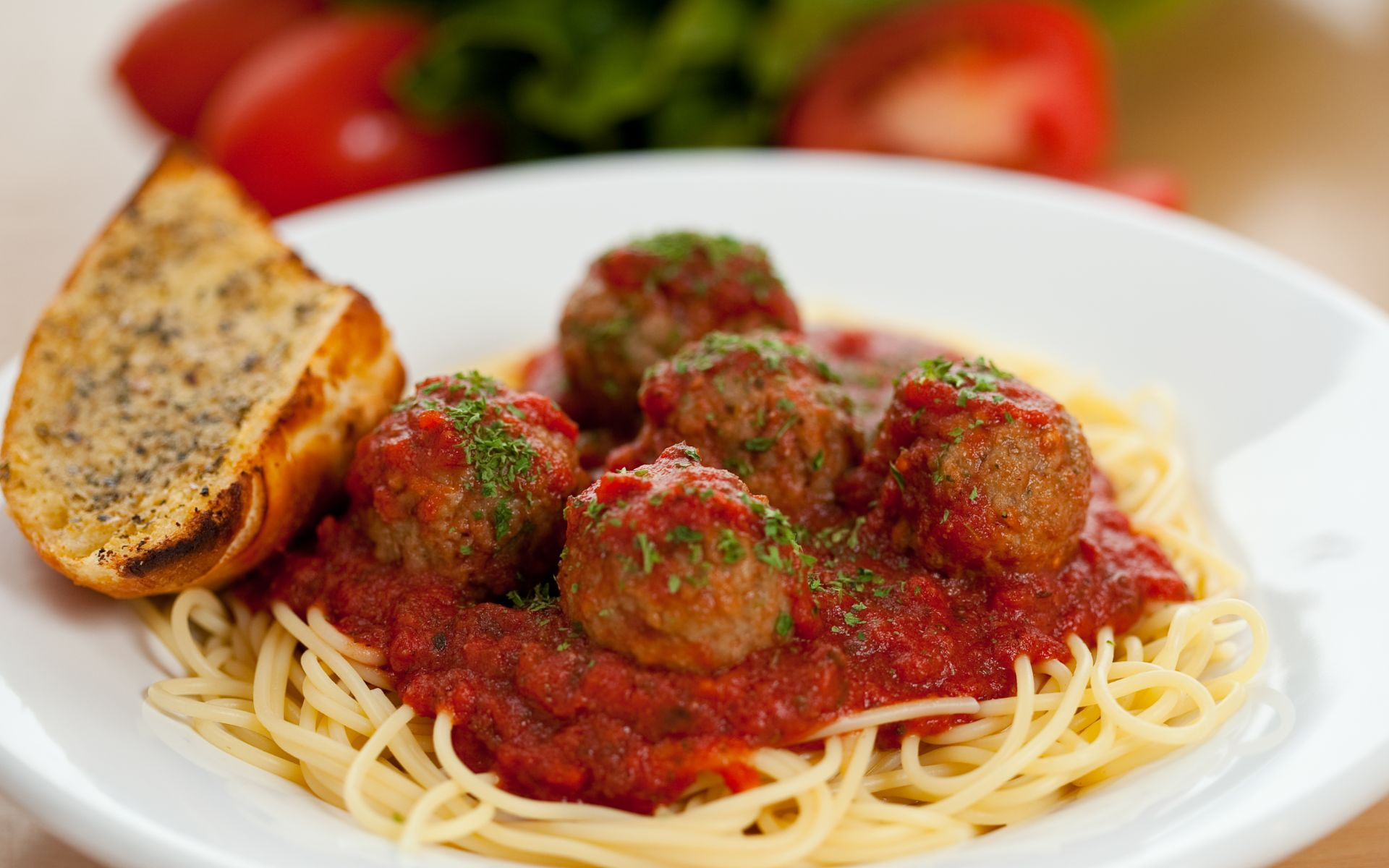 Spaghetti and meatballs in a bowl with garlic bread