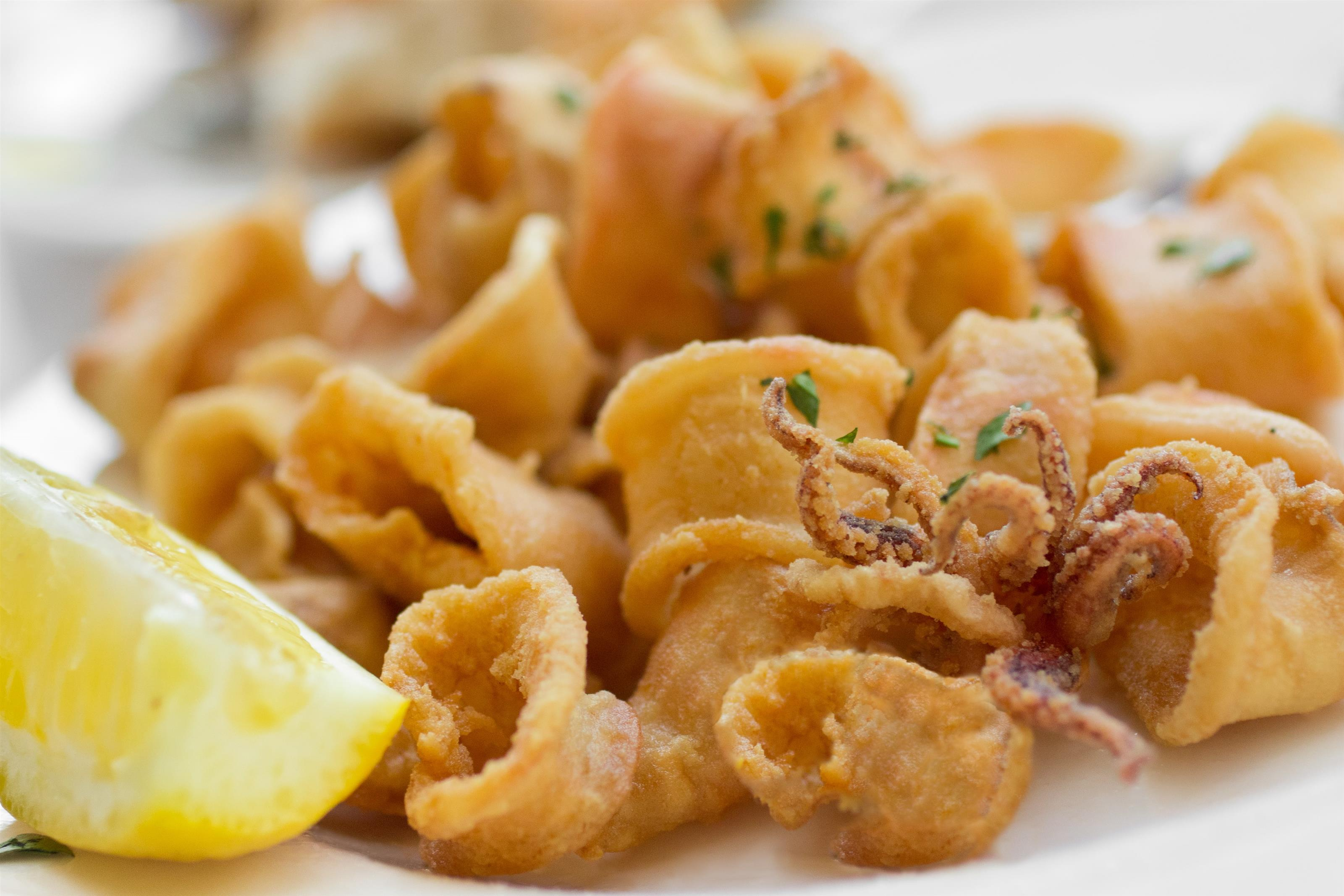 Fried calamari on a plate with a lemon wedge
