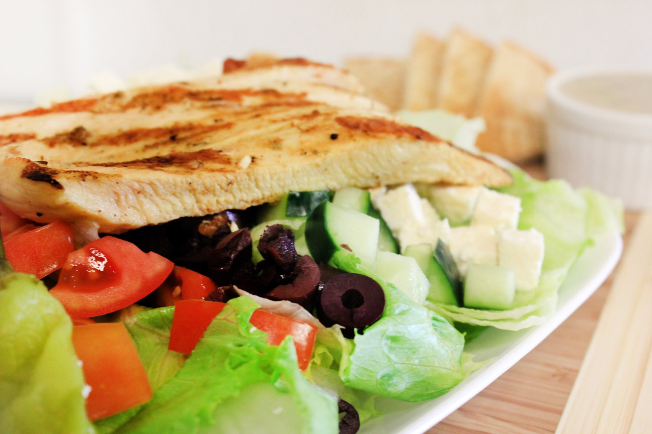 greek salad topped with feta cheese, olives, tomatoes and grilled chicken