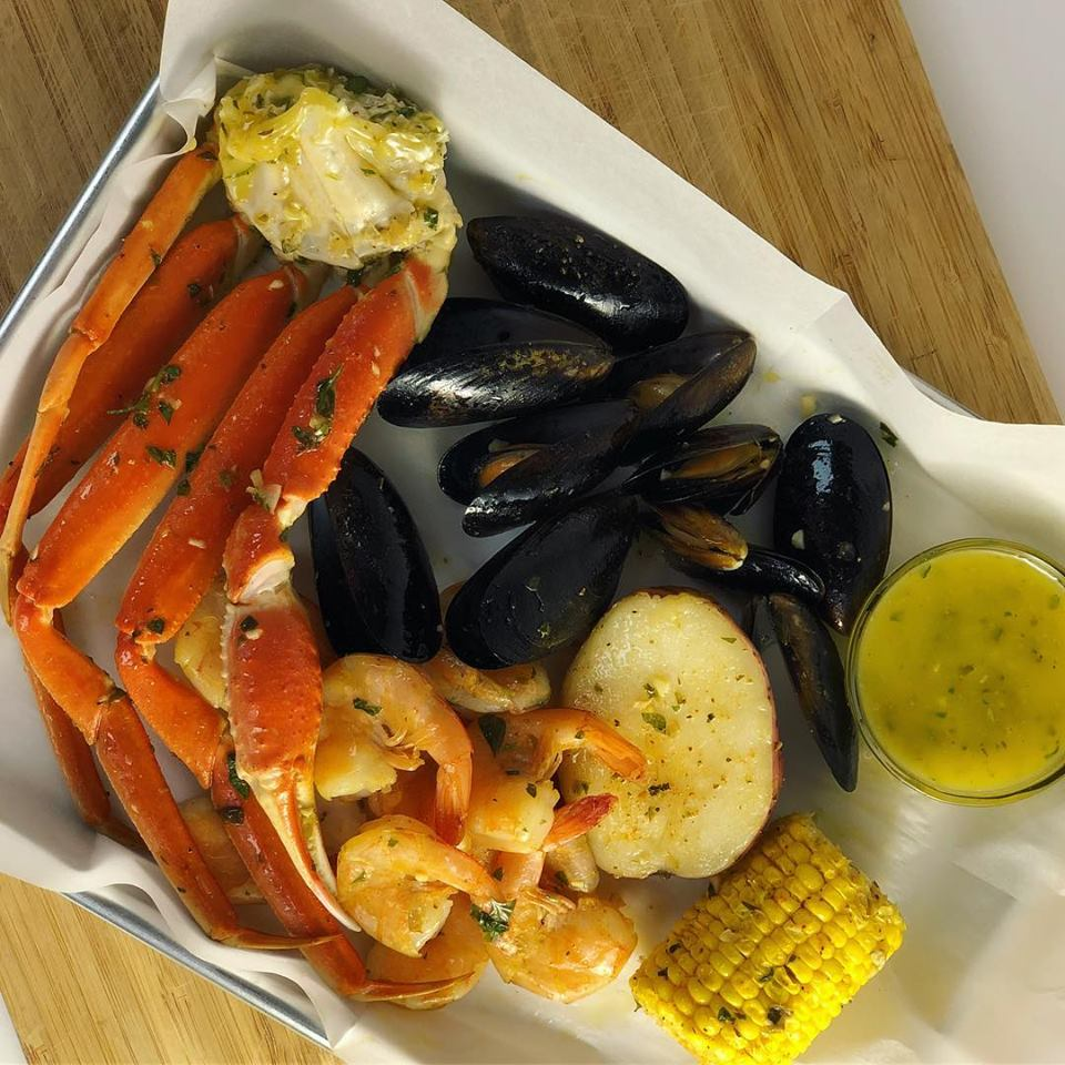 seafood entree with mussels, crab legs, potatoes and corn