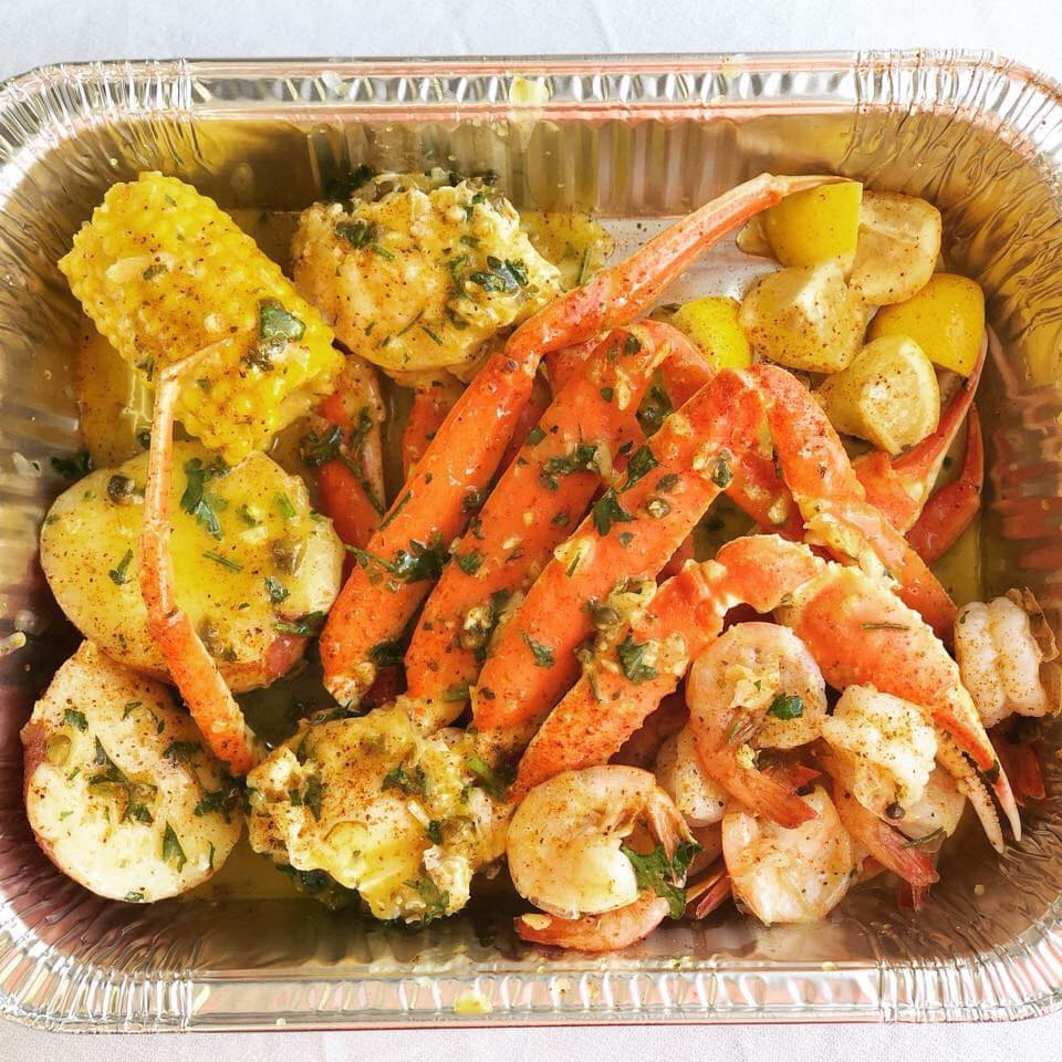 seafood entree with cooked crab legs, shrimp, potatoes ancd corn