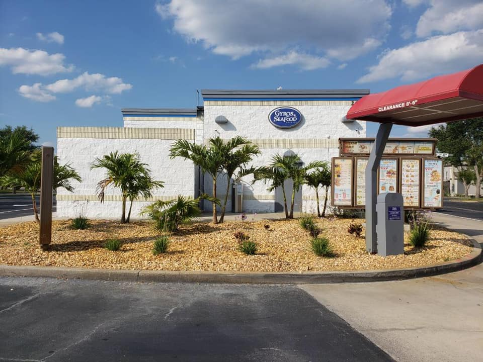 exterior building to gyros & seafood express with a drive-thru area surrounded by palm trees