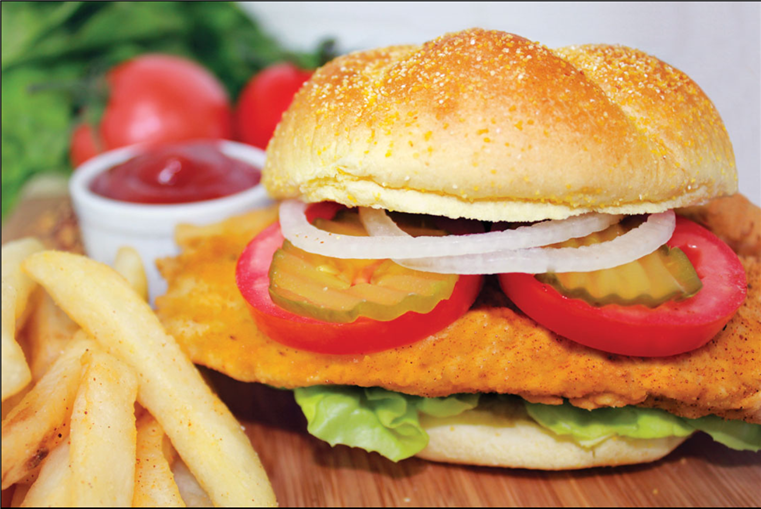 fried fish sandwich with lettuce, tomato, onion, and pickles. French fries and ketchup on the side.