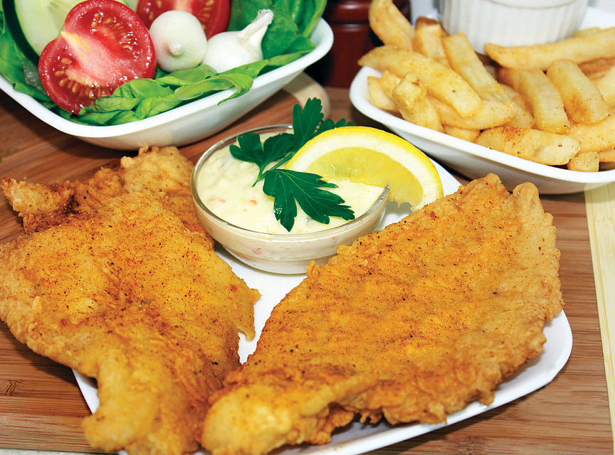 two pieces of fried fish fillet with a side salad and french fries.