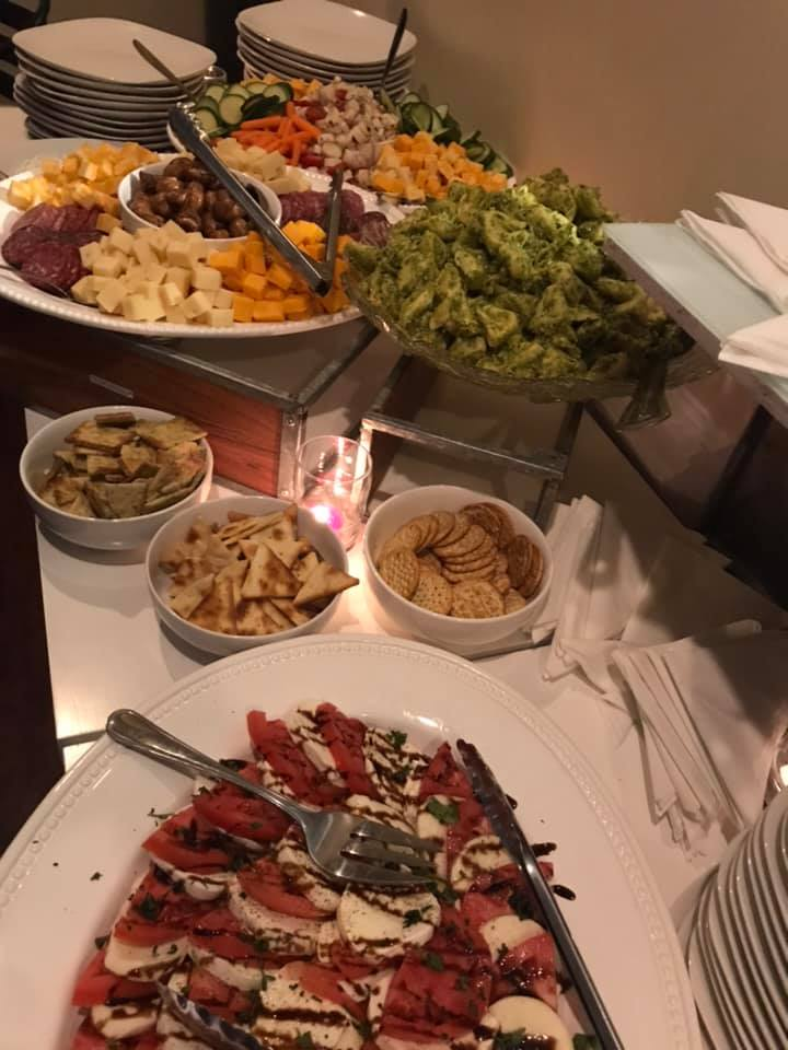 An assortment of meats and cheese with mixed vegetables on plates for a catering event