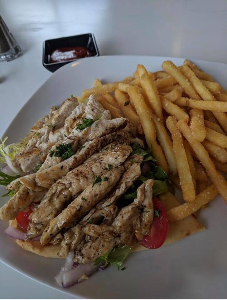 Grilled chicken souvlaki over pita bread with fries
