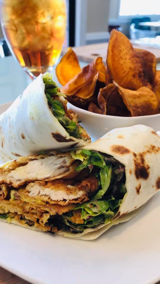 Crispy chicken wrap with lettuce and cheese and a side of potato chips