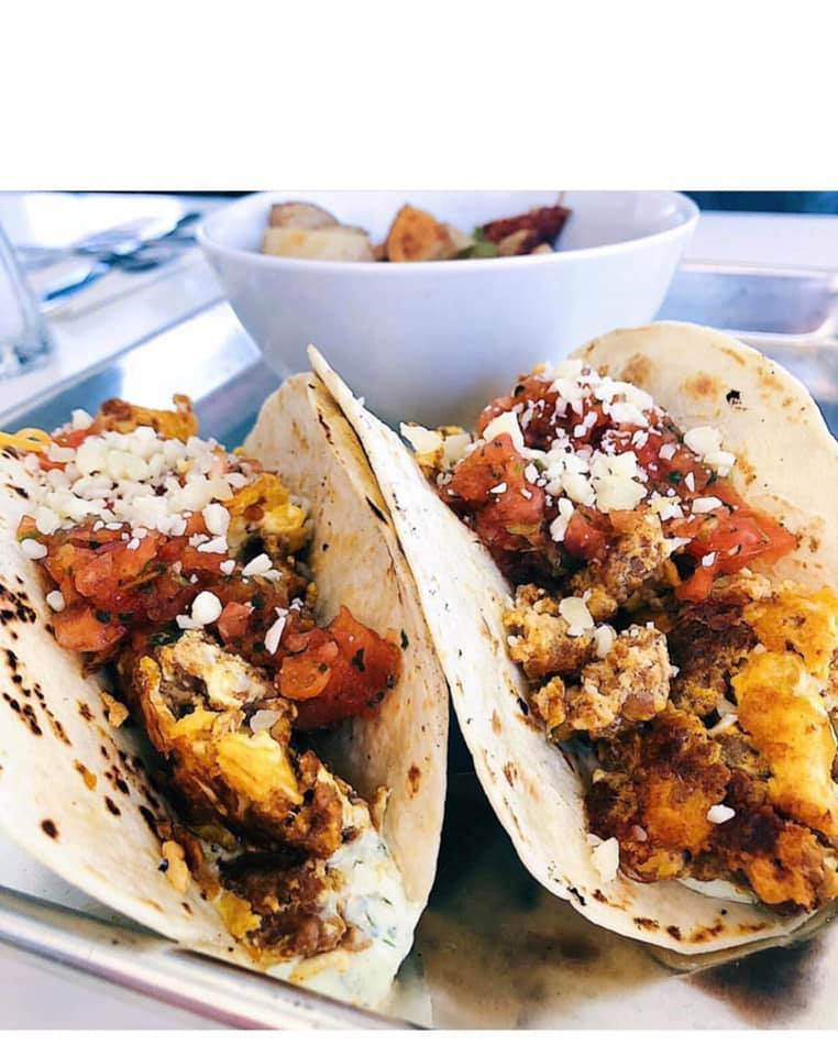 Two Chorizo breakfast tacos on a plate topped with grated cheese