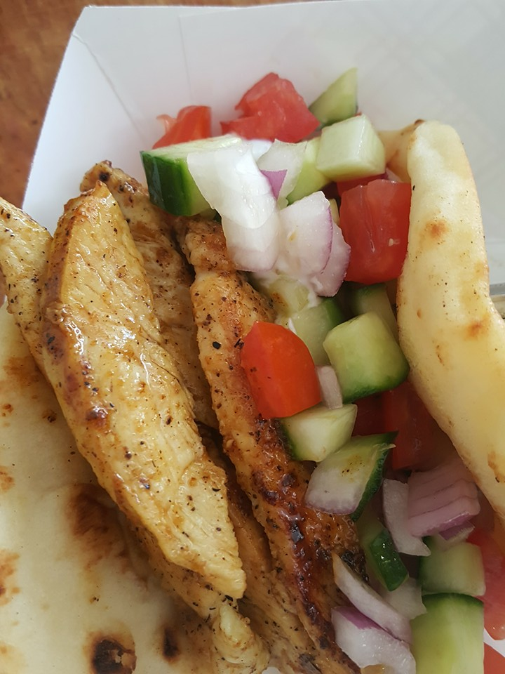 Grilled chicken in a pita with tomatoes, cucumbers and onions