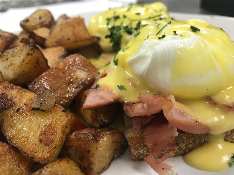 An open egg sandwich topped with ham, burrata, and hollandaise sauce with a side of homefries.