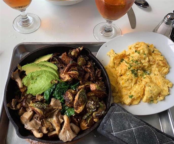 Chicken with spinach and topped with avocado on a hot plate with a side of scrambled eggs