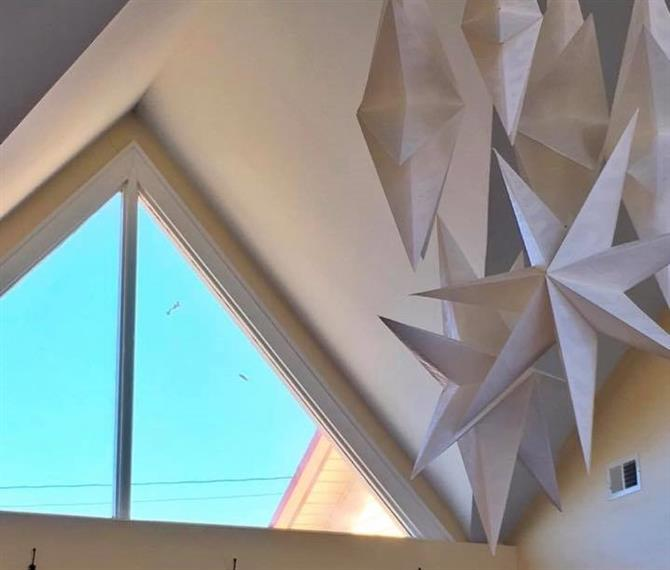 A Triangular shaped window with a peak ceiling and giant paper 3d stars hanging from the ceiling