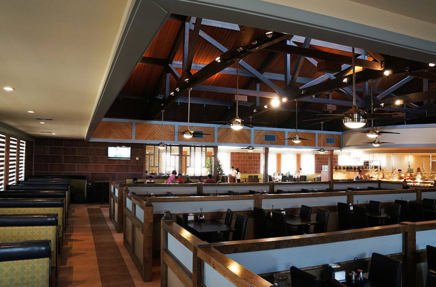 Interior of a building with wooden booths and wooden ceiling with lights that are hanging from wooden beams