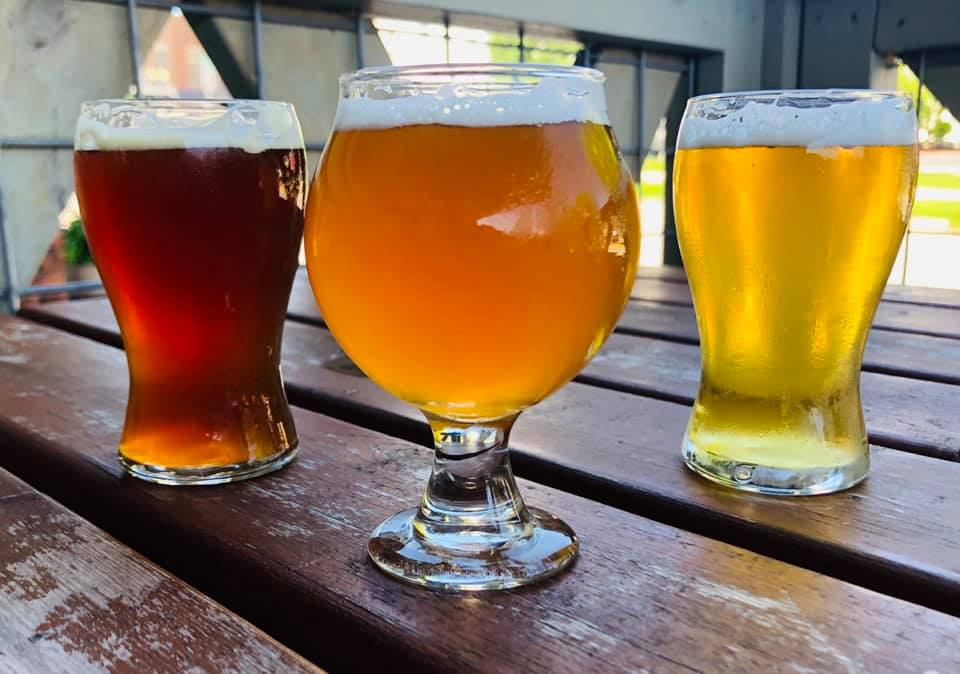 3 types of beers on a wood table outside