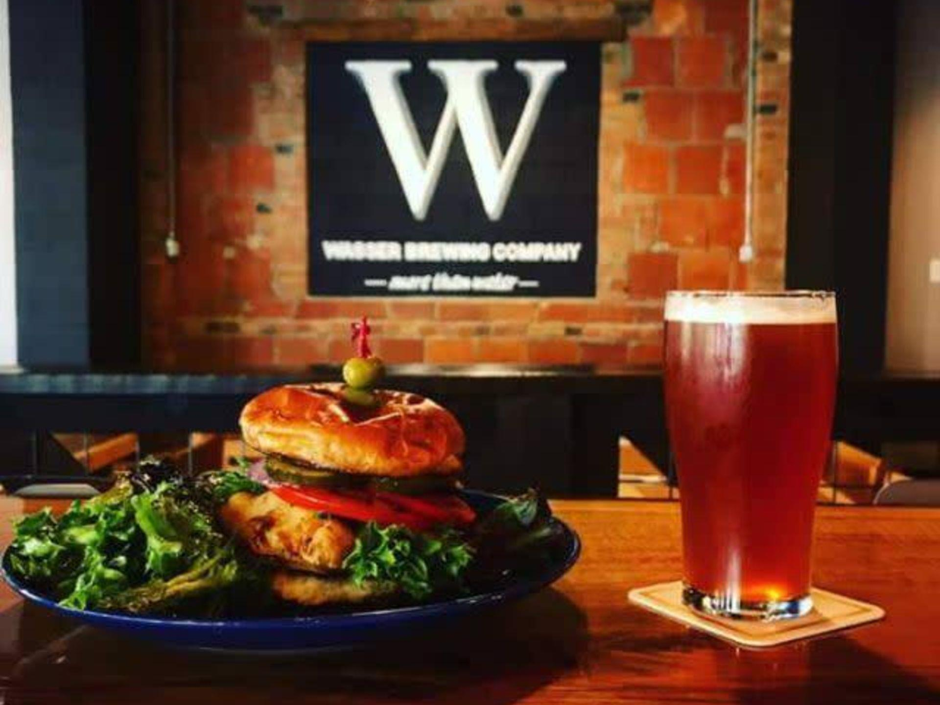Grilled chicken burger with roasted red peppers, pickles and lettuce with a mixed green salad and a pint of beer