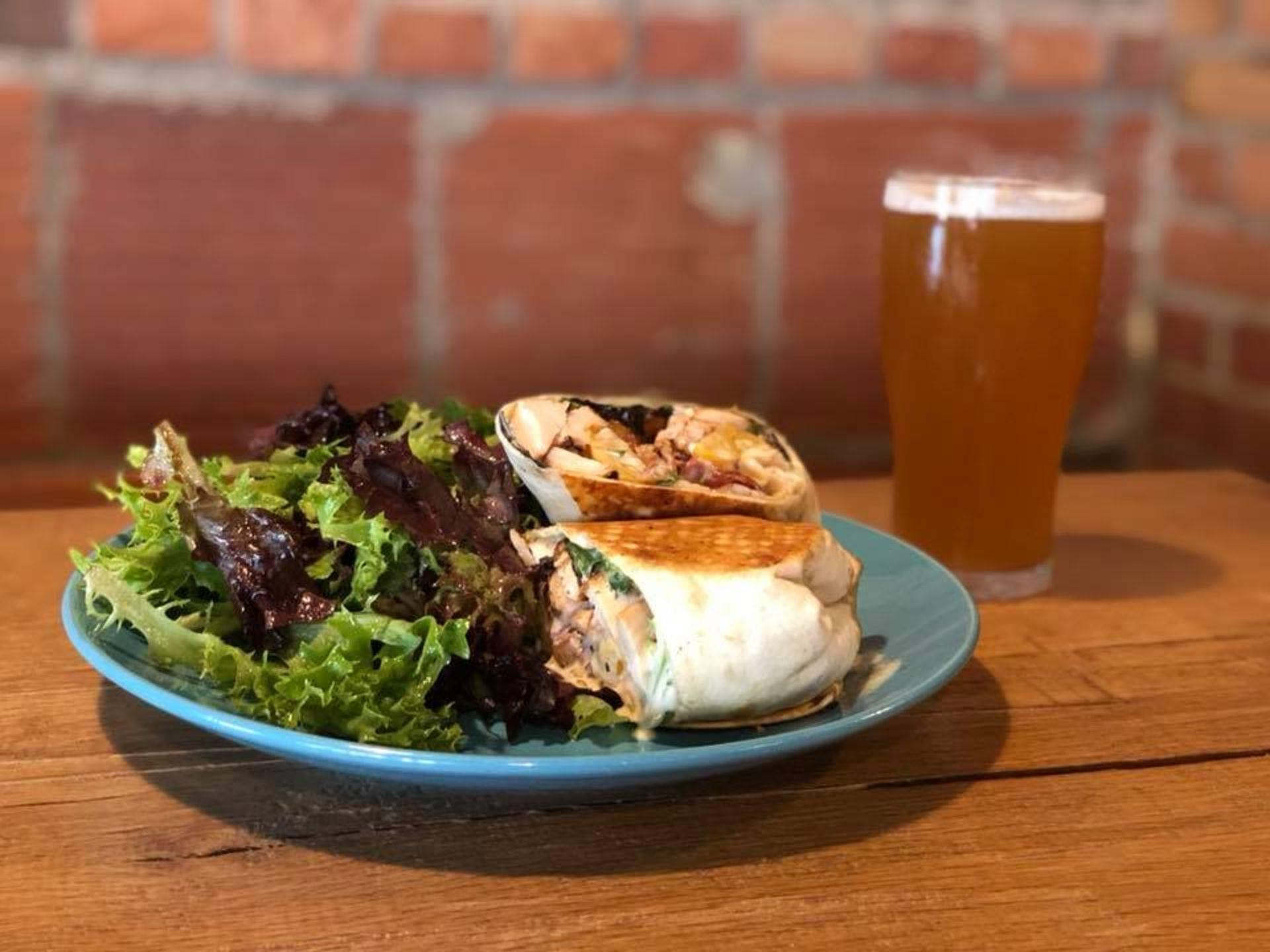 Grilled chicken wrap on a plate with a mixed green salad and a beer