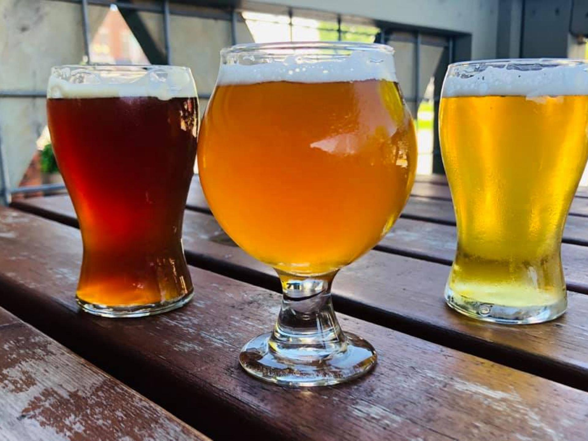 Three assorted beers on a wood table