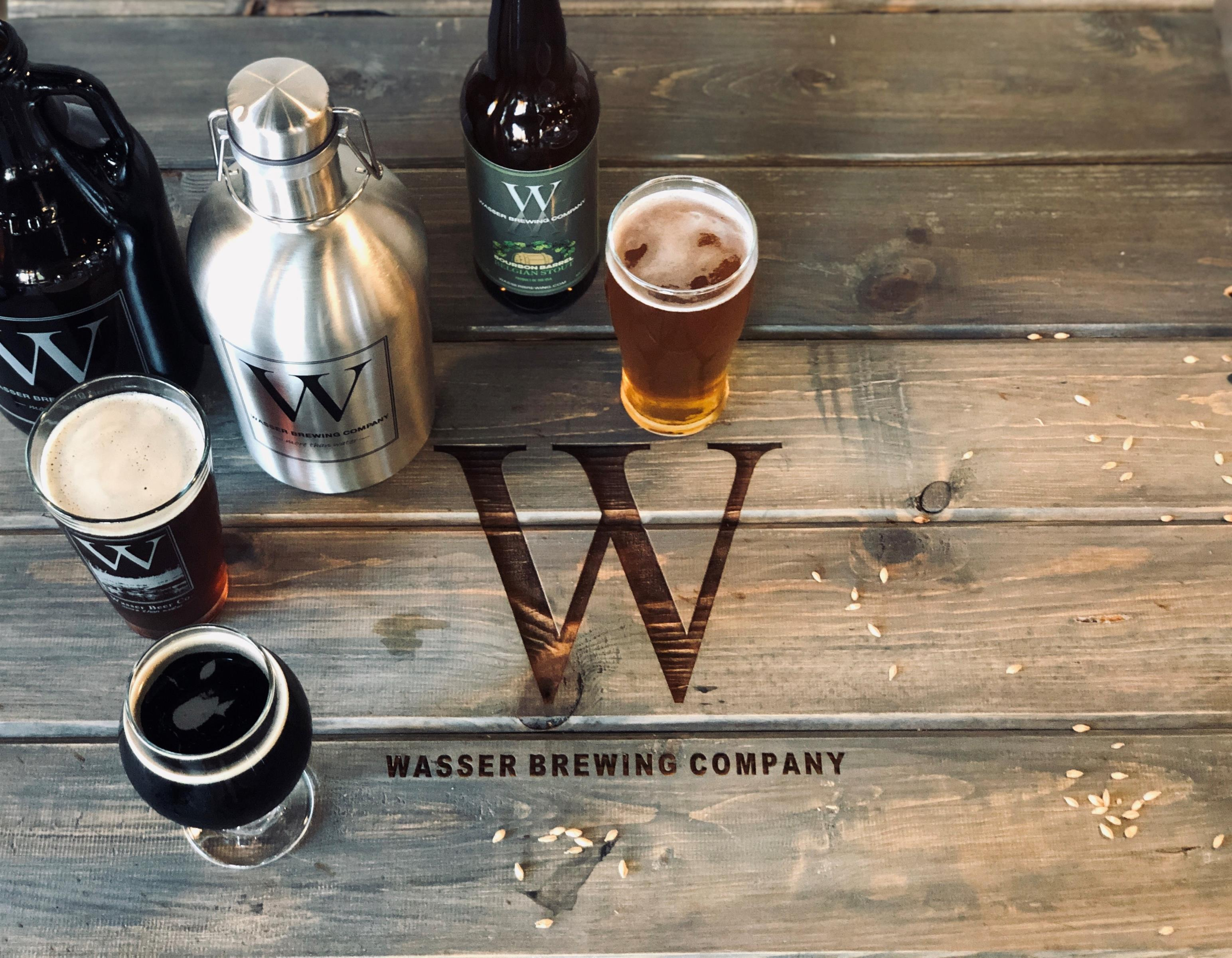 several wasser beer bottles and a pint on a wood table with the wasser brewing co sign engraved