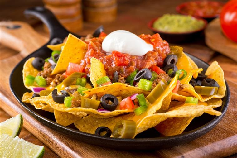 loaded nachos with salsa, olives, peppers, and sour cream