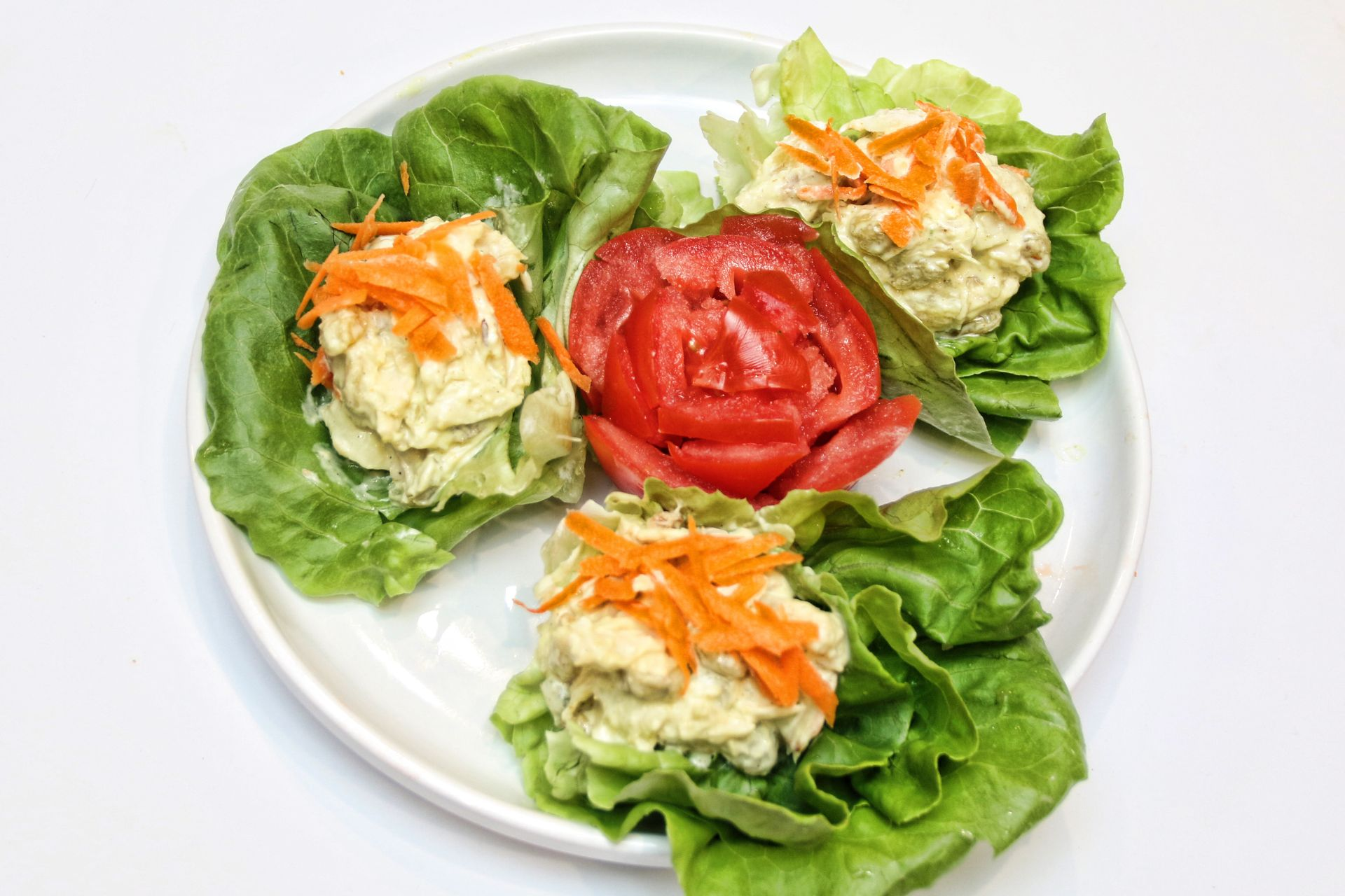 Chicken salad on beds of lettuce topped with shredded carrots and a sliced tomato