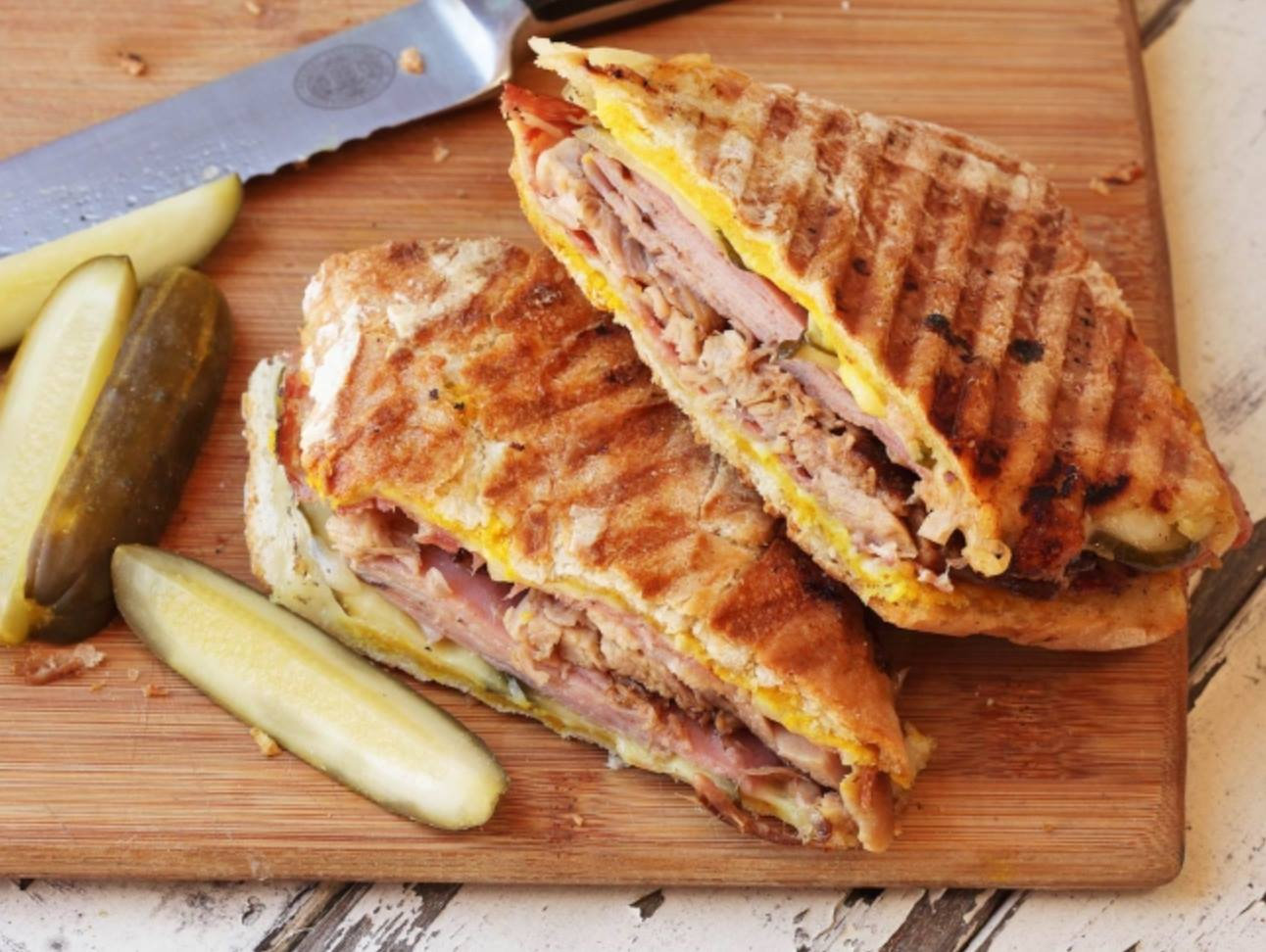 pressed cuban sandwich with mustard on a wood cutting board with a pickle spear