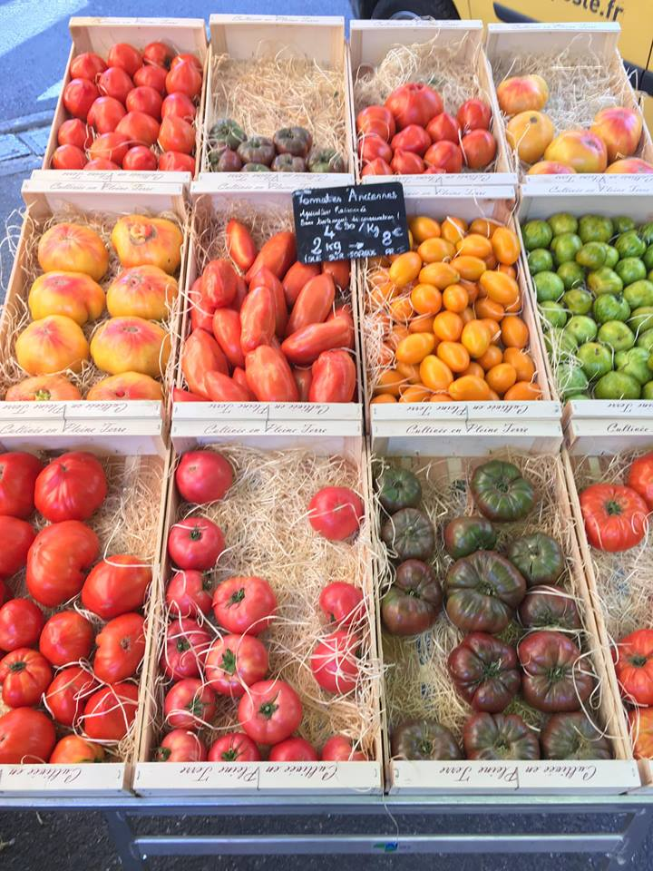 fruits and vegetables set up on a farm stand outside