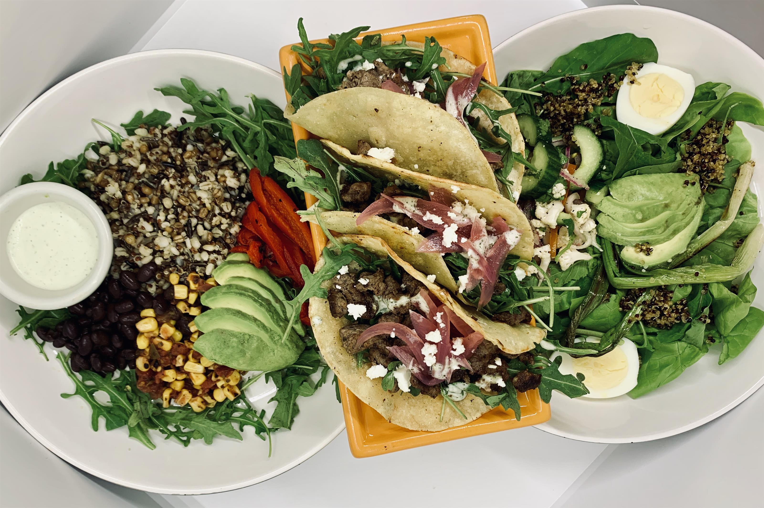 a salad with quinoa, beans, corn, lettuce, avocado, red peppers, and a white dressing. a salad with spinach, quinoa, cucumbers, avocado, and egg. 3 soft tacos with meat, cheese, and arugula.