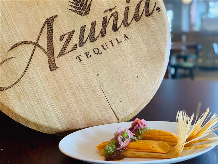 Azunia Tequila logo on wood with a plate of churos in front