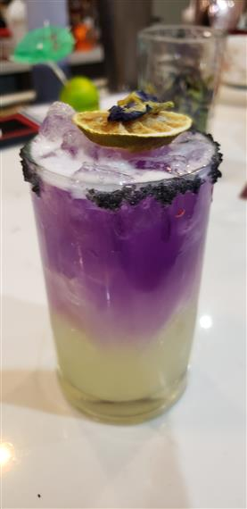 mixed alcoholic drink with different layers and a sugar rim