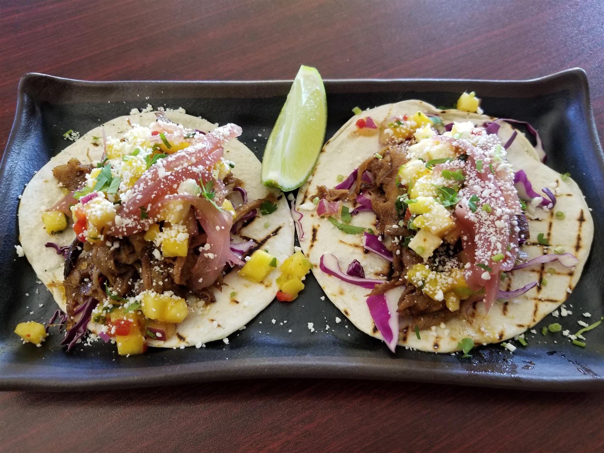plate with 2 tacos with meat and pineapple salsa, garnished with a lime