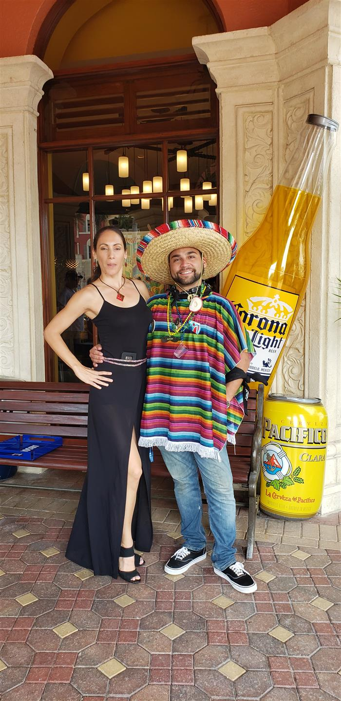 2 people smiling - 1 is wearing a sombrero and a poncho standing in front of a large carona light bottle and pacifico can