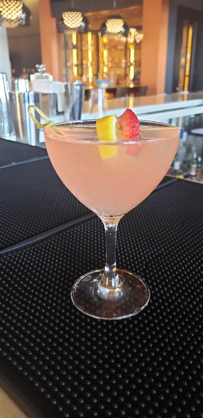 signature pink cocktail garnished with lemon and strawberry