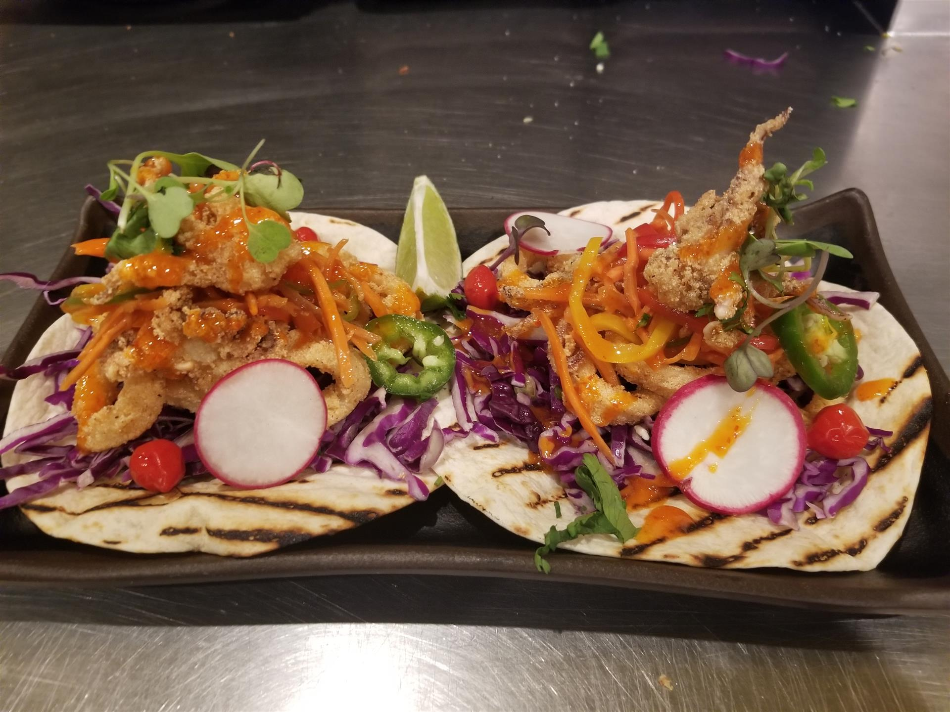 two tacos with calamari, carrot, purple cabbage, bell pepper and sweet-spicy Thai Chili sauce
