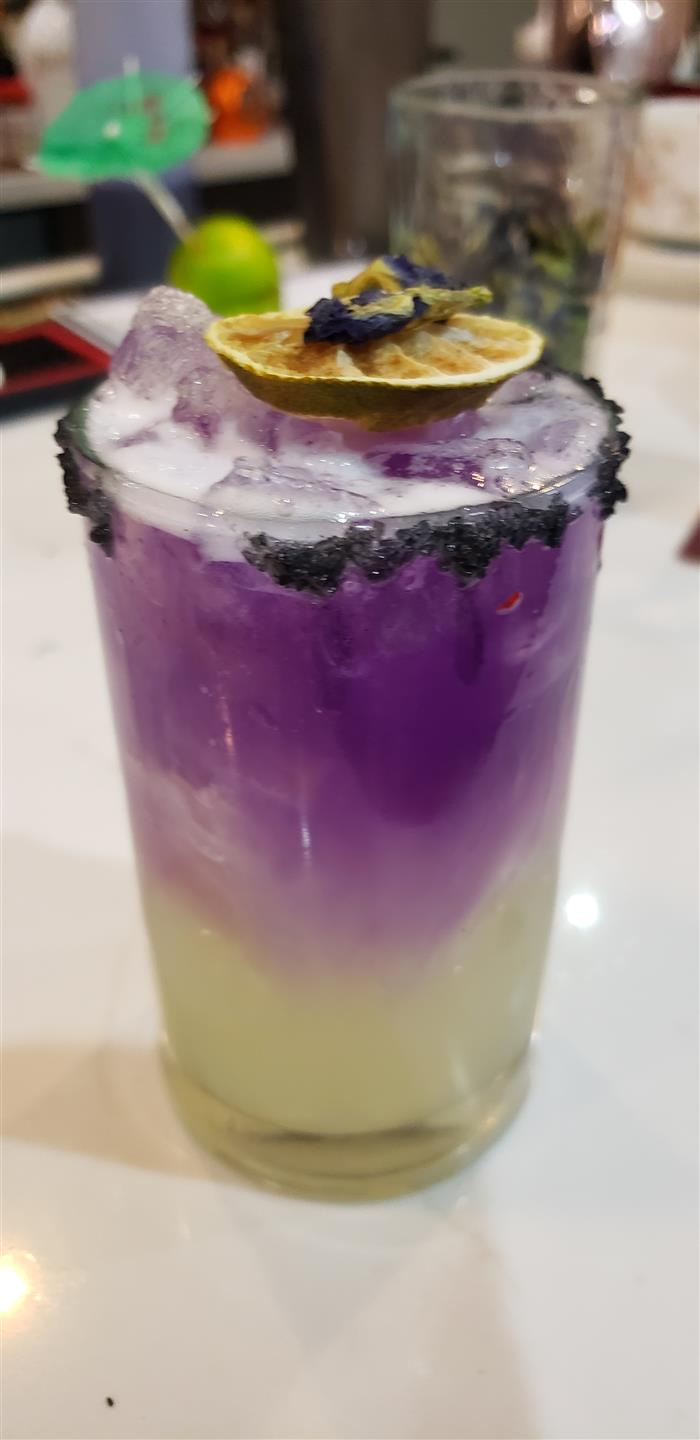 Signature cocktail with a blackberry rim