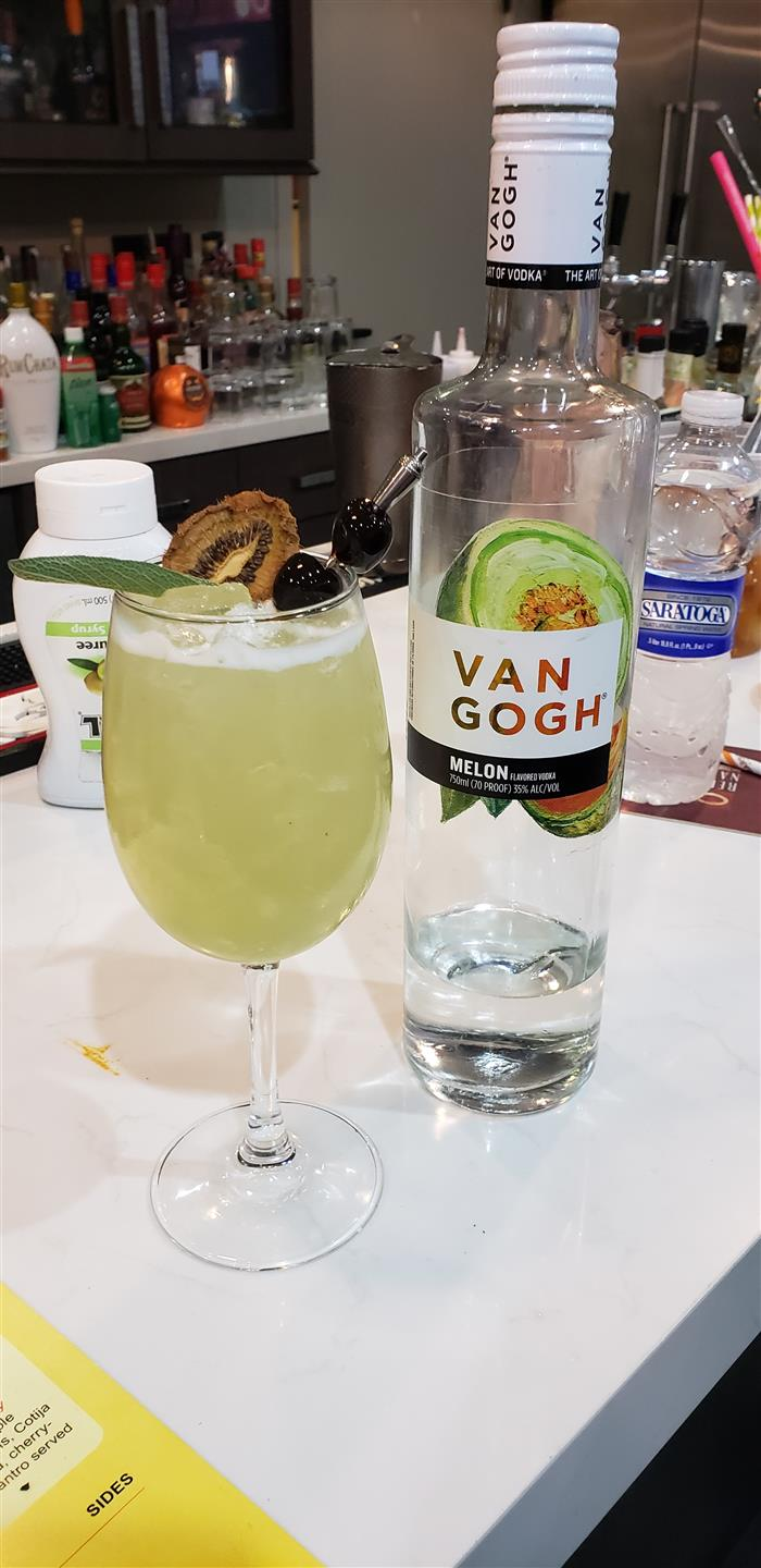 Melon cocktail with Van Gogh alcohol garnished with cherries and a kiwi