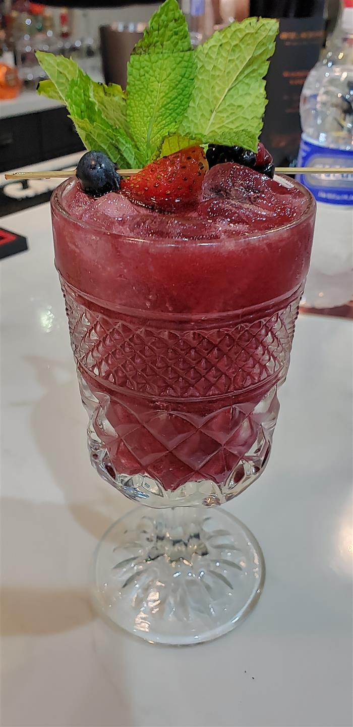 singature red cocktail garnished with a strawberry