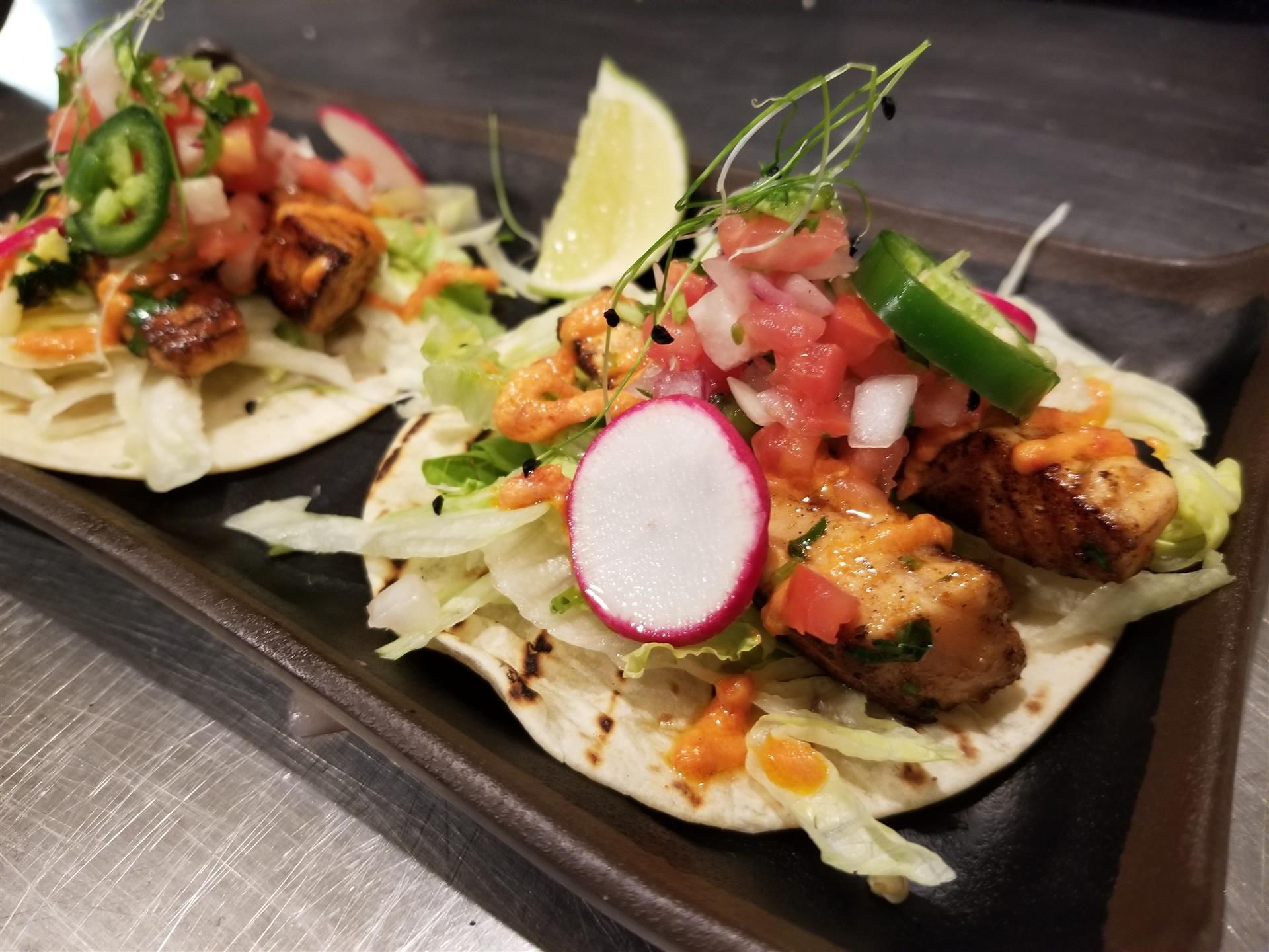 Two chicken tacos with radish, jalapeno and salsa on flour tortillas