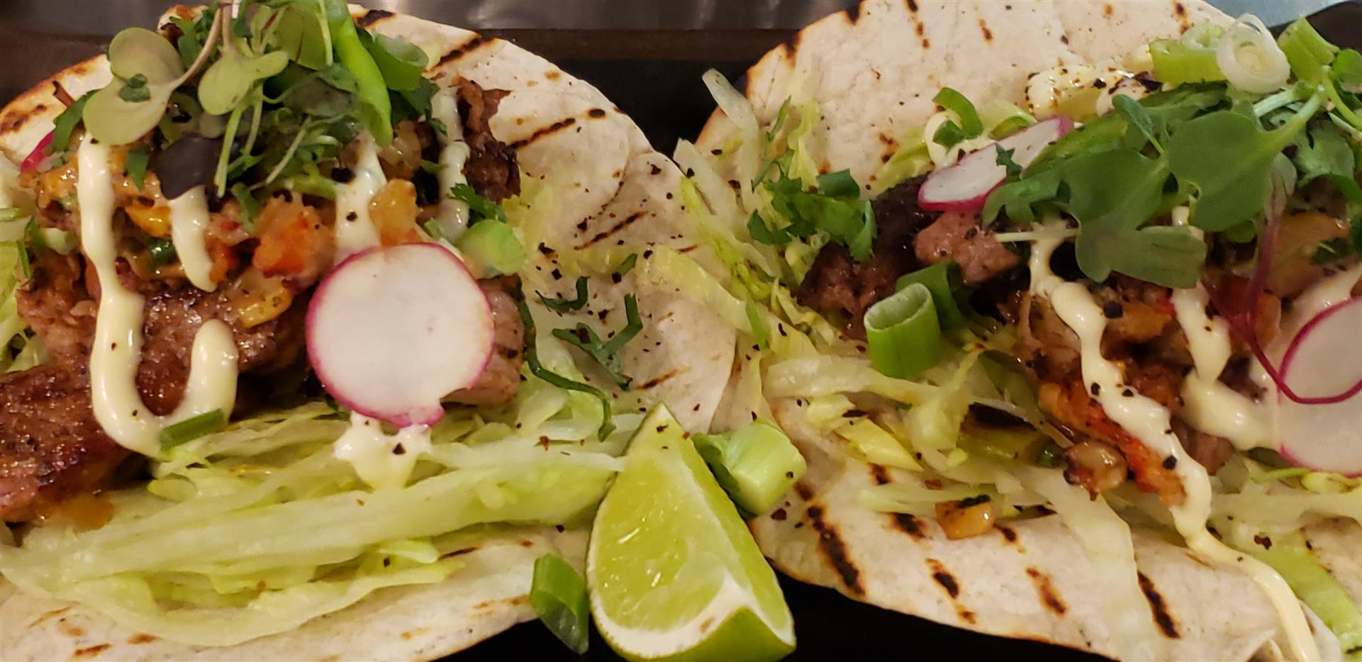 two tacos with meat, radish, scallions and lettuce on flour tortillas