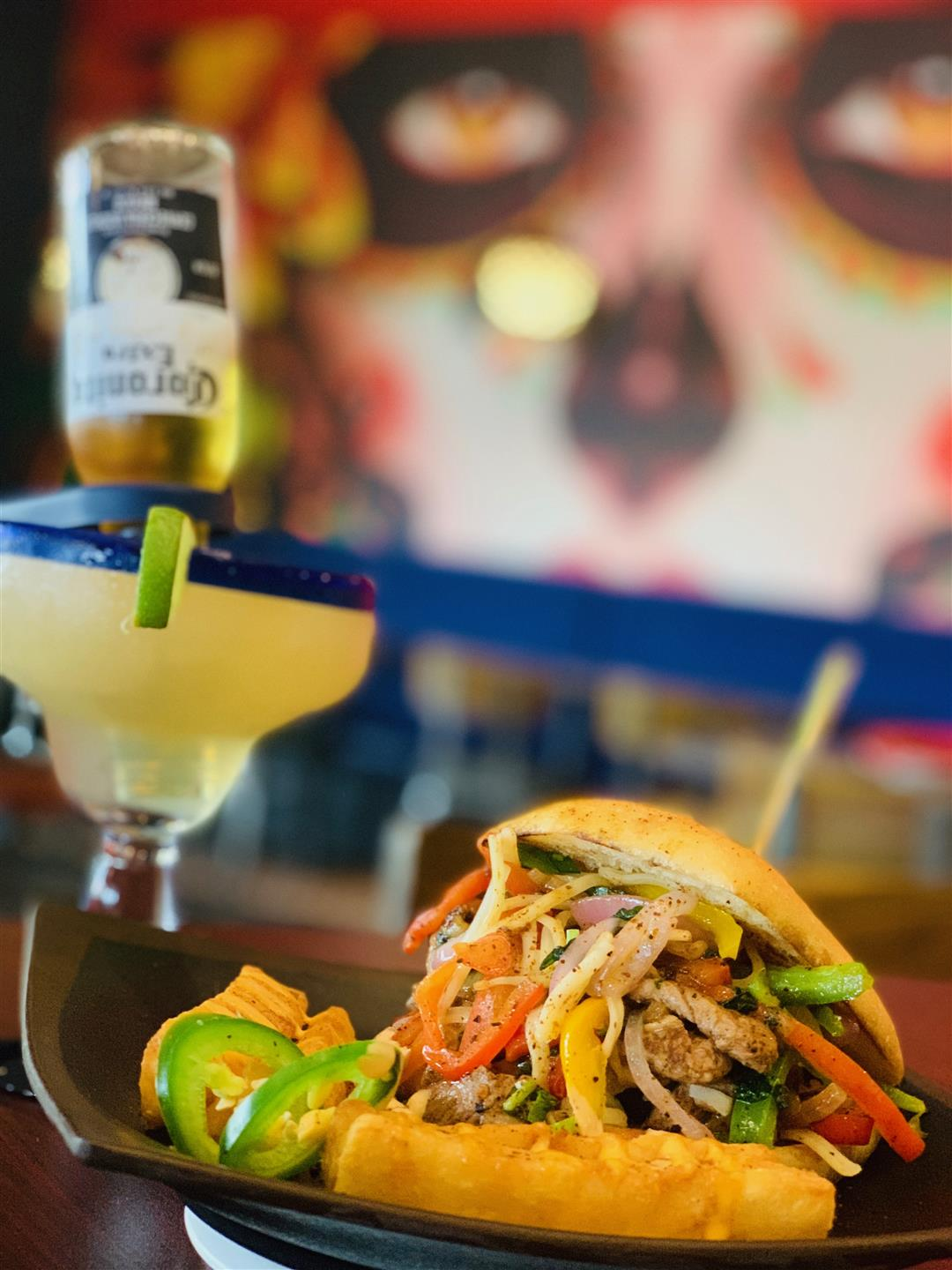 Mexican philly steak torta with steak, bell pepper trio, lettuce, onions and cheese on a toasted torta roll with a corona margarita on the side