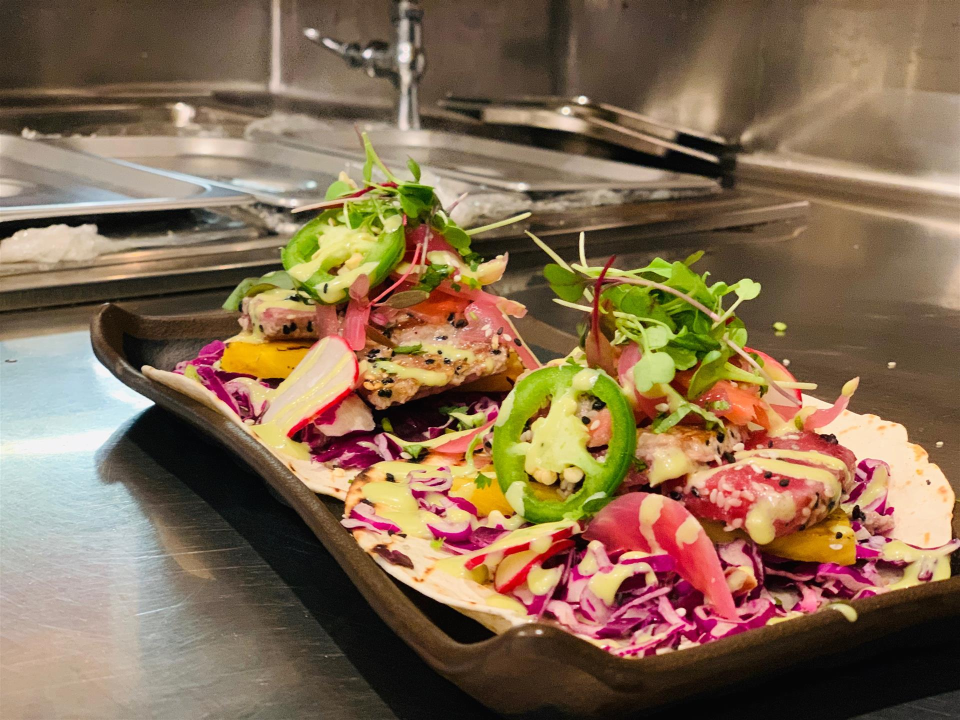 Two Seared ahi tuna tacos with red cabbage, pineapple, pickled onion & cream sauce, sesame seeds.