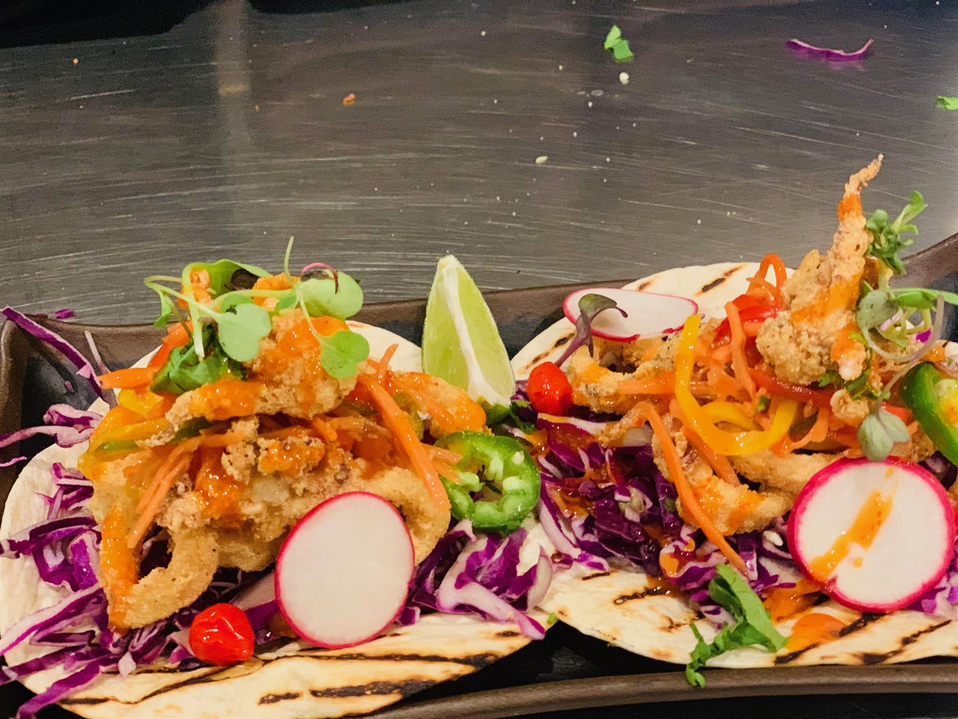 Two calamari tacos with pickled carrots, radishes, purple cabbage and jalapeños on flour tortillas
