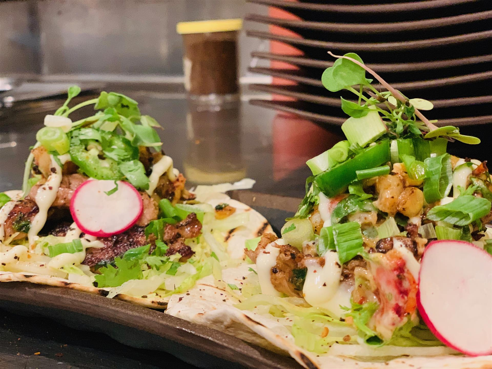 Two tacos with lettuce, scallions, radish and choice of meat on flour tortillas