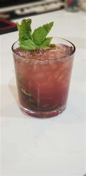 alcoholic beverage with mint leaf garnish in a short glass