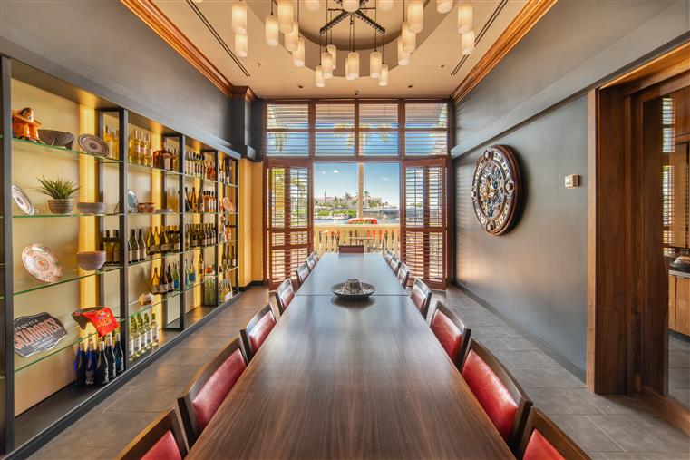 private tequila room with a large long table down the center and shelves of alcohol on the walls with a large floor to ceiling window at the end of the room