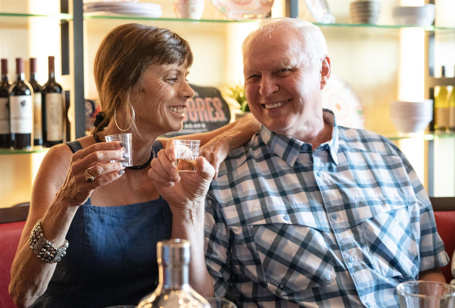 An older couple smiling while posing with their shots