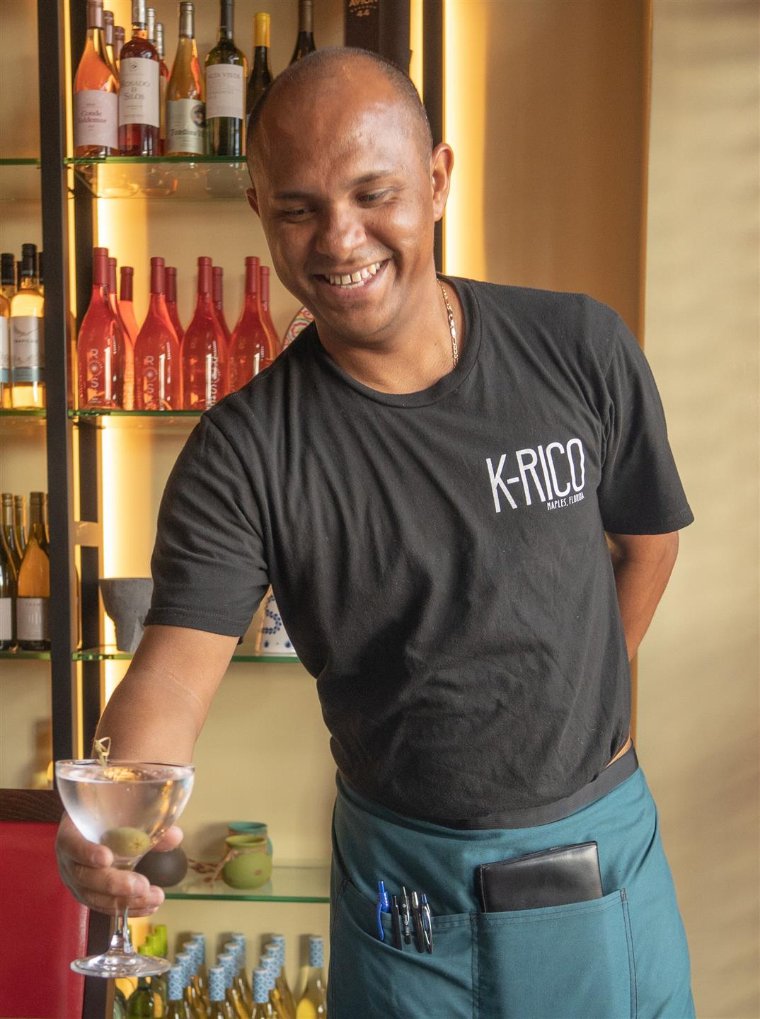 bartender smiling while handing over a drink