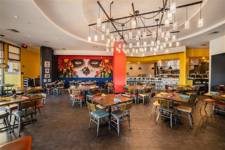 interior of k-rico mexican grill: tables and chairs with napkins on each table in a basket.  There is a mural on the back wall of face with flowers and sugar skull makeup