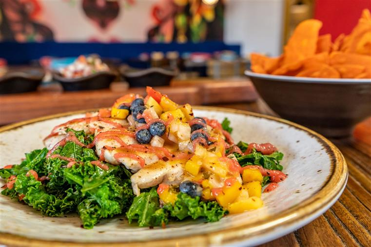 dish with kale, and meat with a fruit salsa on top