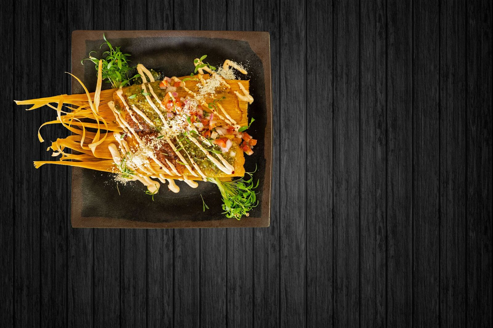top shot of a menu item with Rico de gallo, Cotija cheese and cream sauce drizzled on top